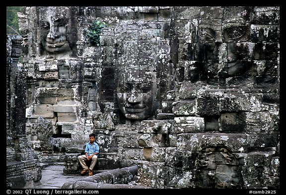 Boy sits next to large stone smiling faces, the Bayon. Angkor, Cambodia (color)