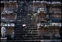 Boy climbs near-vertical staircase, Angkor Thom complex. Angkor, Cambodia (color)