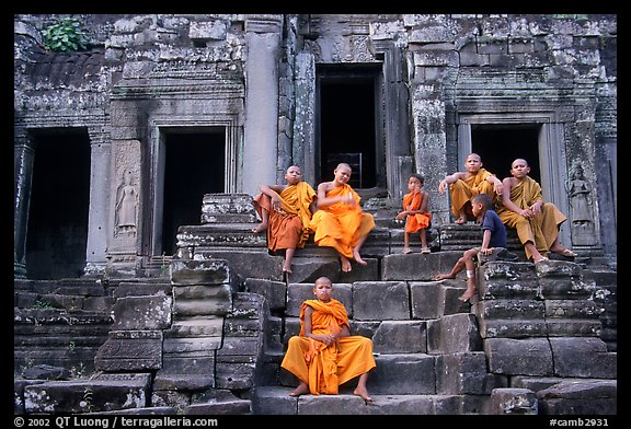 Buddhist monks sitting on steps, Angkor Wat. Angkor, Cambodia