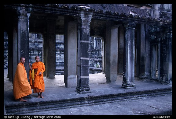 Two Buddhist monks in dark temple, Angkor Wat. Angkor, Cambodia