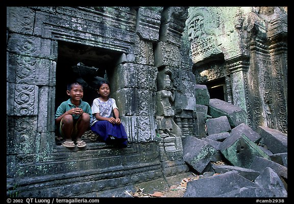 Boy and girl sit at window in Ta Prom. Angkor, Cambodia (color)