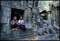 Boy and girl sit at window in Ta Prom. Angkor, Cambodia