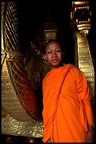Buddhist novice monk, grinning because demonstrating ordained monks style of robe draping. Luang Prabang, Laos