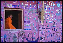 Buddhist novice monk sits at window of shrine, Wat Xieng Thong. Luang Prabang, Laos (color)