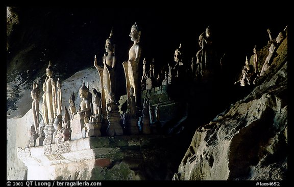 Hundreds of wooden Buddhist figures on wall shelves, Pak Ou caves. Laos (color)