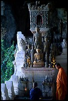 Novice Buddhist monk and vistor in Pak Ou cave. Laos (color)
