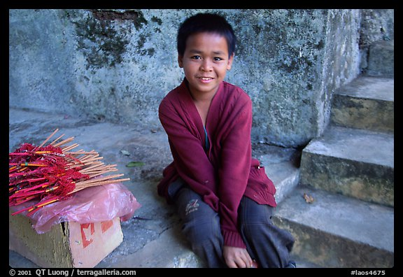 Boy sells incence sticks at the entrance of a shrine, Pak Ou. Laos (color)