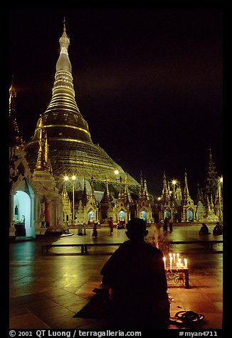 Praying at the wish-fullfilling place by night , Shwedagon Paya. Yangon, Myanmar (color)