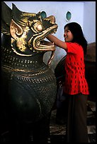 Rubbing an Angkor bronze statue at Mahamuni Paya. Mandalay, Myanmar ( color)