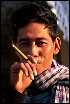 Man enjoying a cheerot (burmese cigar). Mandalay, Myanmar (color)