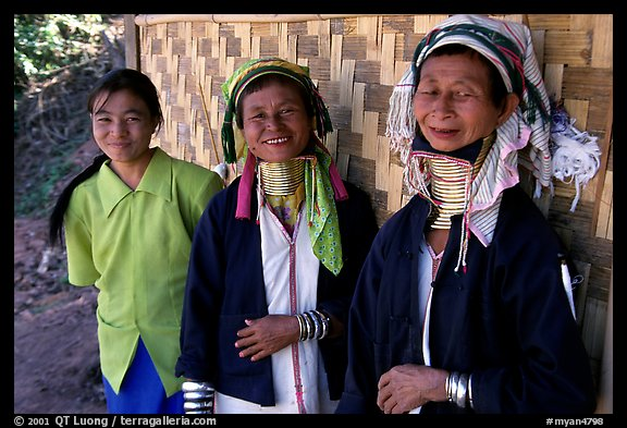 Three generations of Padaung women	along hut. Shan state, Myanmar