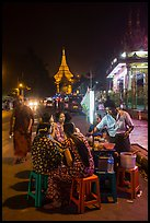 Women eating at street stall at night with Shwedagon Pagoda in background. Yangon, Myanmar ( color)