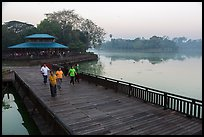 People walking for exercise at dawn, Kandawgyi Lake Park. Yangon, Myanmar ( color)