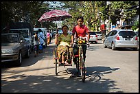 Woman holding unbrella against sun while riding Trishaw. Yangon, Myanmar ( color)
