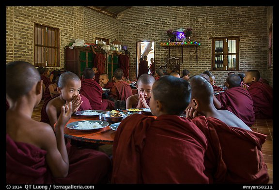 Buddhist novices pray at table before eating lunch, Nyaung U. Bagan, Myanmar (color)