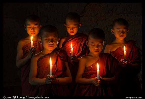 Young buddhist monks holding candles with eyes closed. Bagan, Myanmar (color)