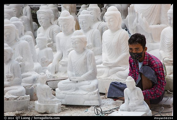 Man working amongst many  buddha statues on Marble street workshop. Mandalay, Myanmar (color)