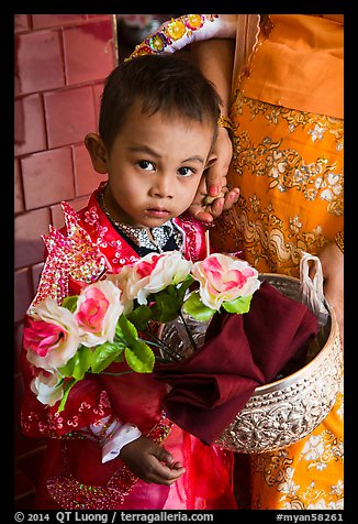 Child carrying offering bowl and flowers for novitiation ceremony, Mahamuni Pagoda. Mandalay, Myanmar (color)