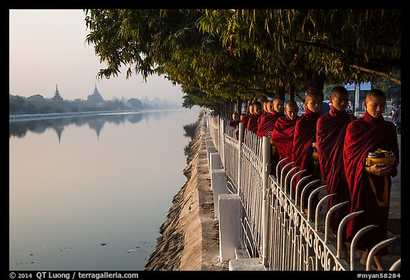 Monks walking in line in alm bowls near Mandalay Fort moat. Mandalay, Myanmar (color)