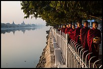 Monks walking in line in alm bowls near Mandalay Fort moat. Mandalay, Myanmar ( color)