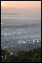 Fog shrouded plain below Mandalay Hill at sunrise. Mandalay, Myanmar ( color)