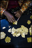 Close-up of hands separating gold leaves. Mandalay, Myanmar ( color)