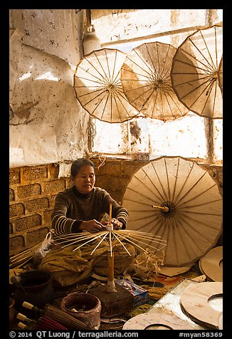 Woman assembling the paper umbrellas carried by the monks. Pindaya, Myanmar (color)