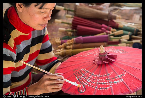 Woman painting the red umbrellas carried by the monks. Pindaya, Myanmar (color)