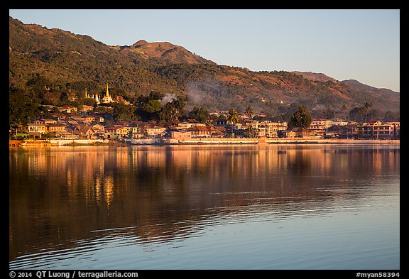 Hill and town reflected in Pone Tanoke Lake at sunrise. Pindaya, Myanmar (color)