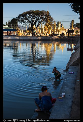 Women washing and doing laundry in lake with pagoda in background. Pindaya, Myanmar (color)