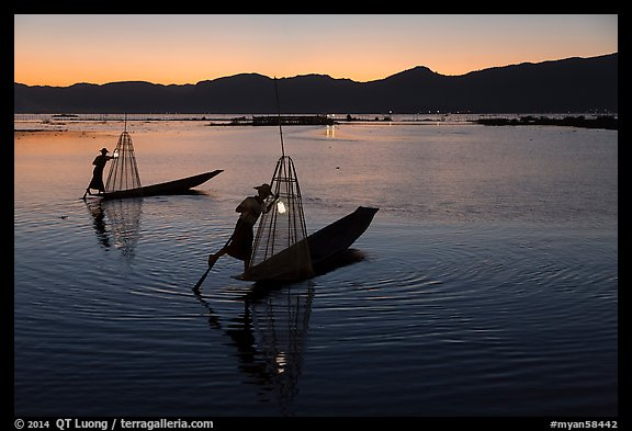 Leg-rowing Intha fishermen with lanterns at dusk. Inle Lake, Myanmar (color)