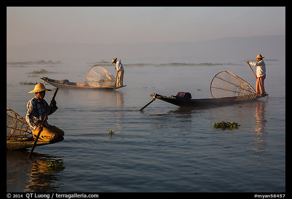 Intha fishermen rowing boats in early morning mist. Inle Lake, Myanmar (color)