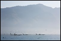 Intha fishermen in the distance using spears to stir fish, below tall hills. Inle Lake, Myanmar ( color)
