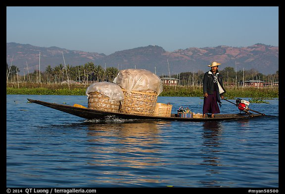 Man transporting baskets on boat. Inle Lake, Myanmar (color)