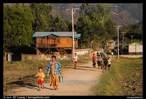 Villagers walking on path to jetty, Maing Thauk Village. Inle Lake, Myanmar (color)
