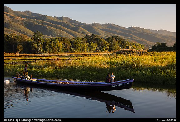 Woman riding with child in front of boat in Maing Thauk Village. Inle Lake, Myanmar (color)