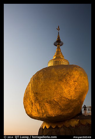 Pilgrim prays to the gleaming Golden Rock at sunset. Kyaiktiyo, Myanmar (color)