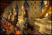 Monks sitting below row of buddha images, Wat Arun. Bangkok, Thailand (color)