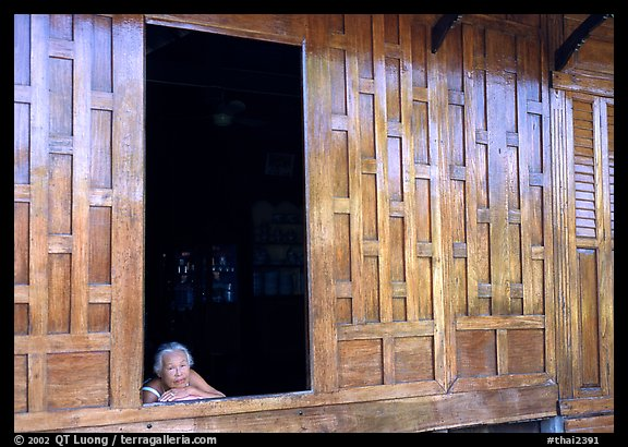 Woman looks out of teak house window. Damonoen Saduak, Thailand