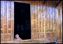 Woman looks out of teak house window. Damonoen Saduak, Thailand ( color)