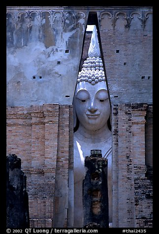 Monumental Buddha image seen between walls,  Wat Si Chum. Sukothai, Thailand