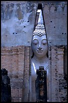 Monumental Buddha image seen between walls,  Wat Si Chum. Sukothai, Thailand (color)