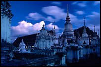Chedis in blue light with bright clouds, Wat Suan Dok, dusk. Chiang Mai, Thailand