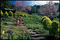 Children in traditinal hmong dress in flower garden. Chiang Mai, Thailand