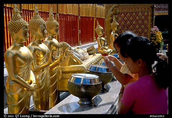 Worshiper makes offering at Wat Phra That Doi Suthep. Chiang Mai, Thailand (color)