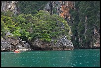 Couple paddling below steep cliffs. Krabi Province, Thailand ( color)
