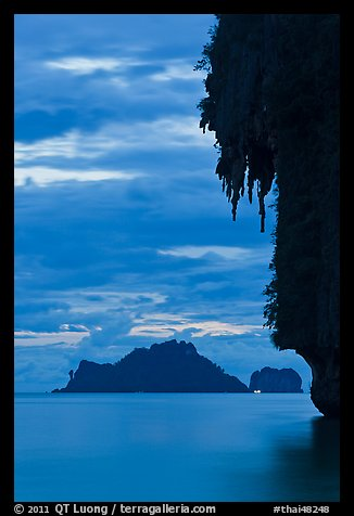Limestone crag with stalactite, distant islet, boat light, Railay. Krabi Province, Thailand