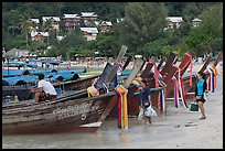 Women returning with shopping bags prepare to board boats, Ko Phi Phi. Krabi Province, Thailand