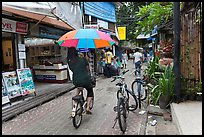 Woman riding bicycle with unbrella, Tonsai village, Ko Phi-Phi Don. Krabi Province, Thailand ( color)