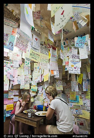 Women eating at Pad Thai restaurant decorated with customer notes, Ko Phi-Phi Don. Krabi Province, Thailand (color)